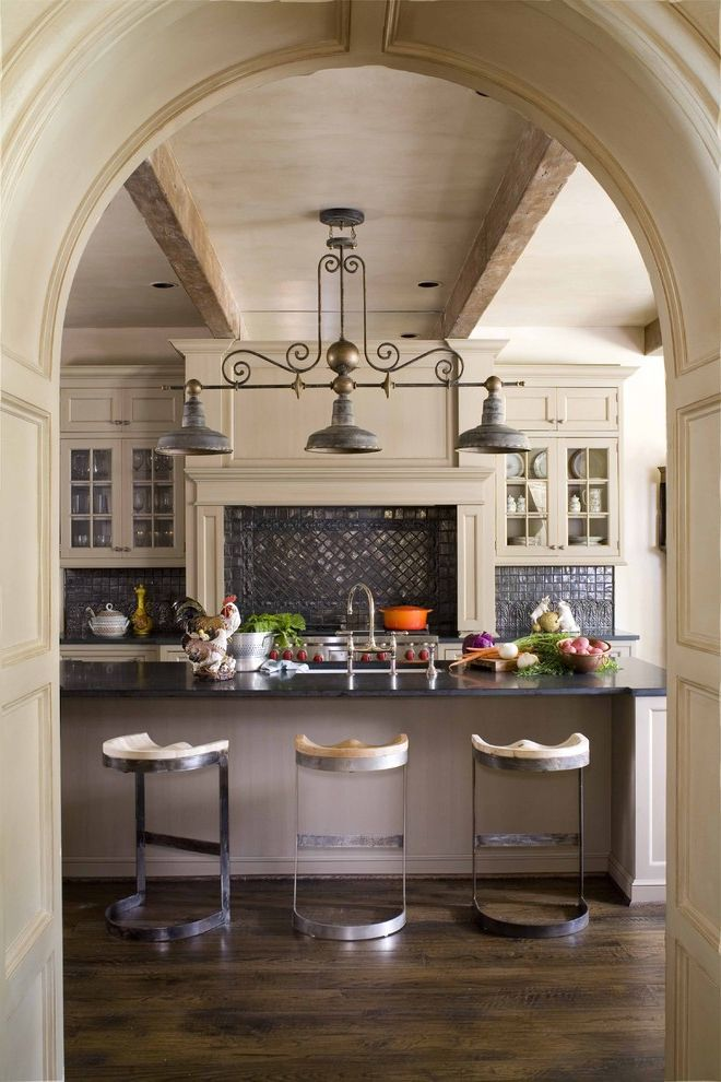 Mission Style Light Fixtures with Traditional Kitchen and Breakfast Bar Dark Floor Exposed Beams Glass Front Cabinets Island Lighting Kitchen Island Eat in Kitchen Neutral Colors Tile Kitchen Backsplash Wood Flooring Wood Paneling