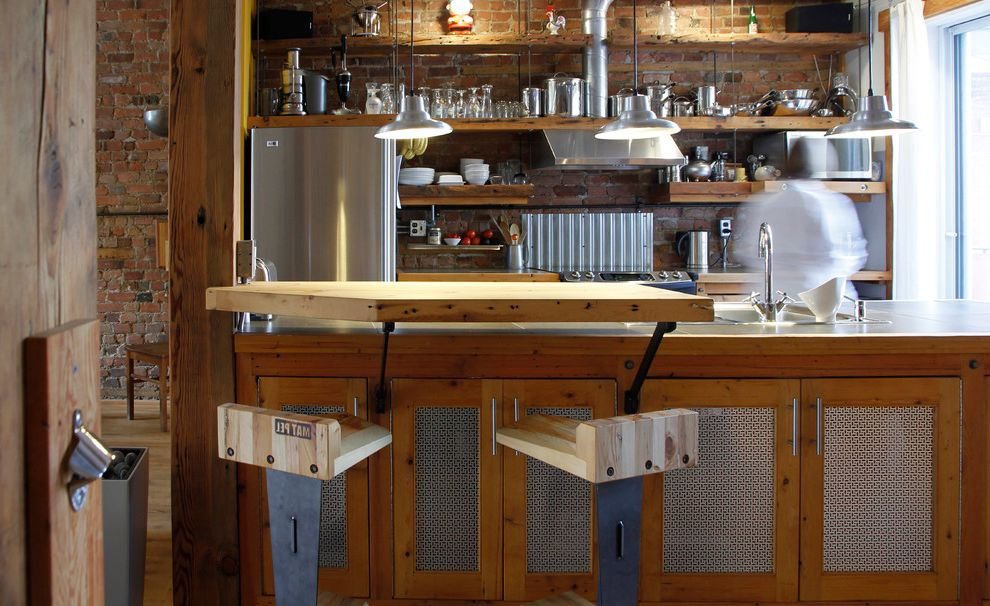 Missoula Electric Coop with Industrial Kitchen  and Breakfast Bar Brick Walls Eat in Kitchen Exposed Brick Industrial Kitchen Island Open Kitchen Open Shelves Pendant Lighting Split Level Island Stainless Steel Appliances Wood Flooring