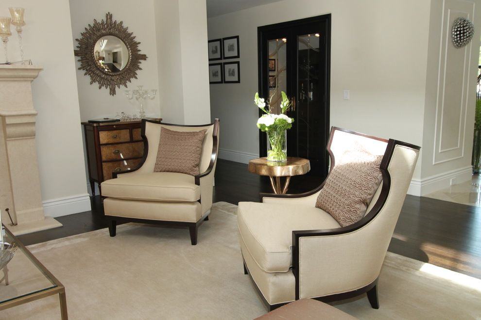 Narrow Accent Chair   Contemporary Living Room Also Area Rug Baseboards Chest of Drawers Dark Floor Glass Coffee Table Neutral Colors Sunburst Mirror Wall Decor Wingback Chair Wood Flooring