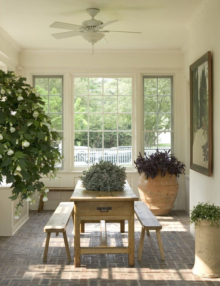 Narrow Farmhouse Table with Traditional Porch Also Atrium Brick Floor Ceiling Fan Conservatory Large Window Molding Olive Urn Potted Plants Radiator Cover Sun Room Urns Wood Bench Wood Table