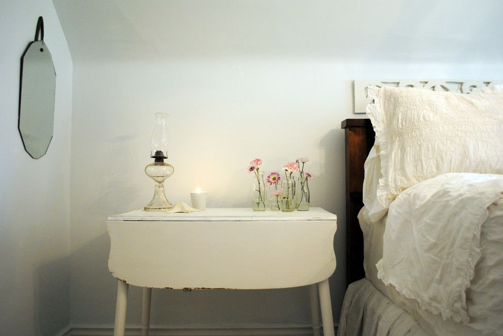 Narrow Night Table   Shabby Chic Style Bedroom  and Bedside Table Cottage Drop Leaf Table Floral Arrangement Frameless Mirror Kerosine Lamp Monochromatic Neutral Colors Painted Wood Shabby Chic Vase White Bedding Wood Headboard