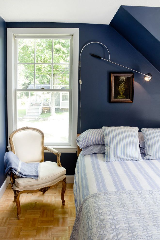 Navy Blue Velvet Chair with Beach Style Bedroom Also Baseboards Dark Walls Louis Chair Navy Blue Walls Parquet Floor Reading Lamp Striped Bedding Swing Arm Lamp White Wood Wood Flooring Wood Trim