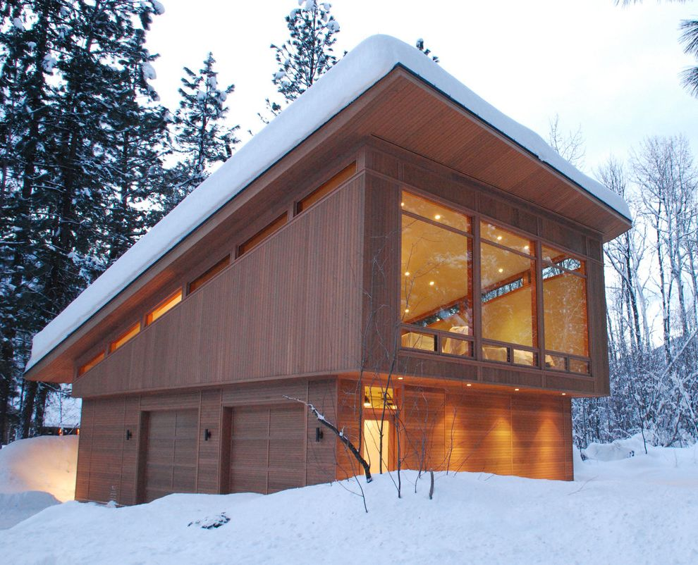 Odyssey House of Utah with Modern Garage  and Clerestory Windows Dark Stained Wood Double Garage Eaves Recessed Lights Slant Roof Snow Tall Windows Wood Siding Wood Soffit