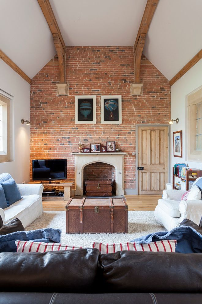Old Fashioned Wall Clock with Farmhouse Living Room and Coffee Table Chest Coffee Table Trunk Exposed Beams Exposed Brick Exposed Brick Wall Fireplace High Ceiling Trunk Unused Fireplace White Couch White Sofa