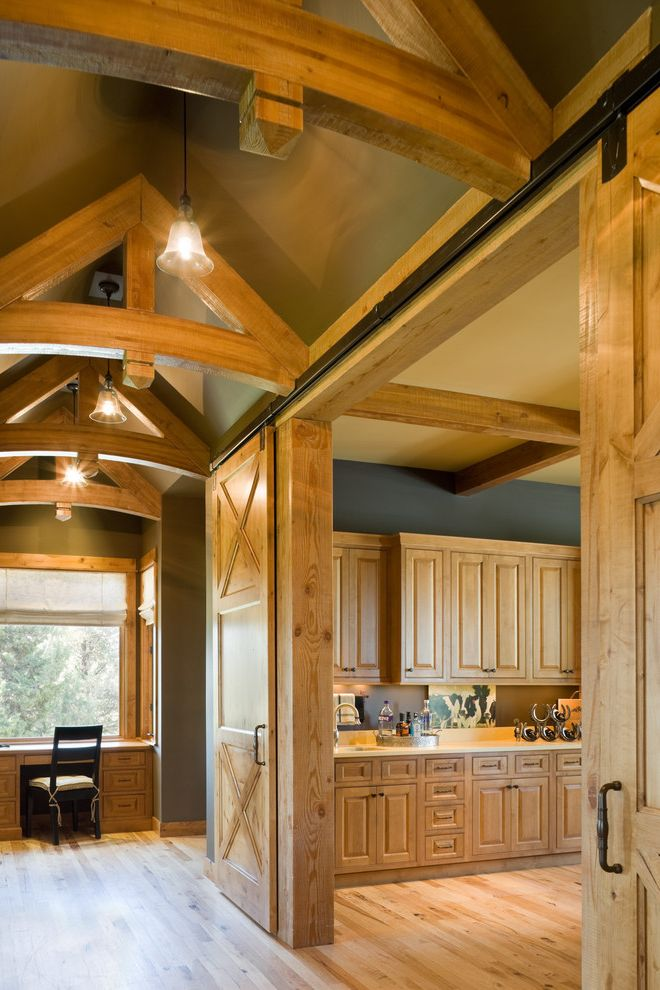 Open the Door in Spanish with Rustic Hall  and Barn Door Beams Black Built in Cabinets Desk Exposed Beams Floor Gray Kitchen Light Light Wood Floors Office Open Truss Ceiling Pendant Pine Posts Rough Hewn Rustic Sliding Barn Door Wood