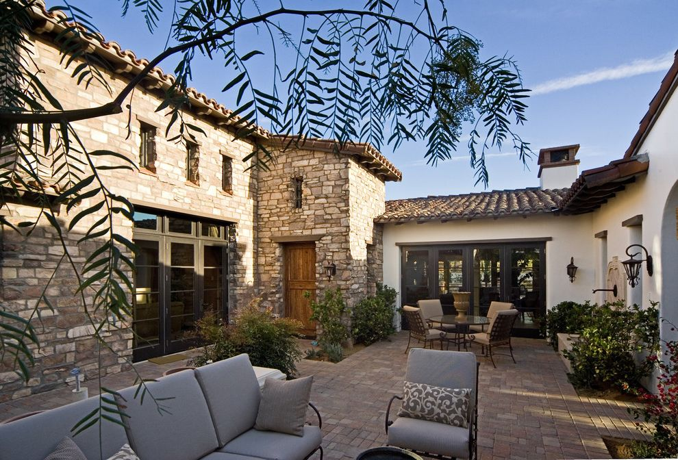 Orco Pavers   Mediterranean Exterior  and Brick Chimney Courtyard Cushions Fountain French Doors Gray Lanterns Lintel Outdoor Seating Patio Pavers Pillows Rustic Door Stone Stone Facade Tile Tile Roof Water Feature