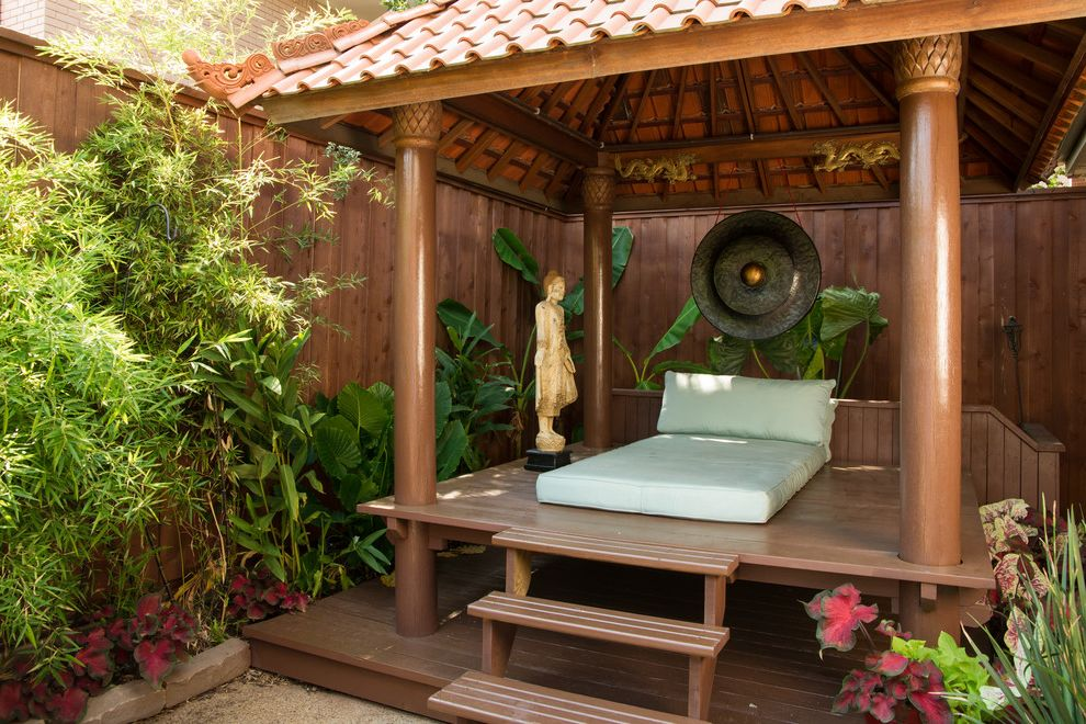 Outdoor Cabana Bed   Asian Deck  and Asian Deck Lounge Seating Bamboo Clay Tile Roof Covered Deck Human Statue Lounge Outdoor Bed Pagoda Palm Capitals Sleeping Area Tropical Landscaping White Cushion Wood Columns Wood Deck Wood Fence Wood Steps Zen