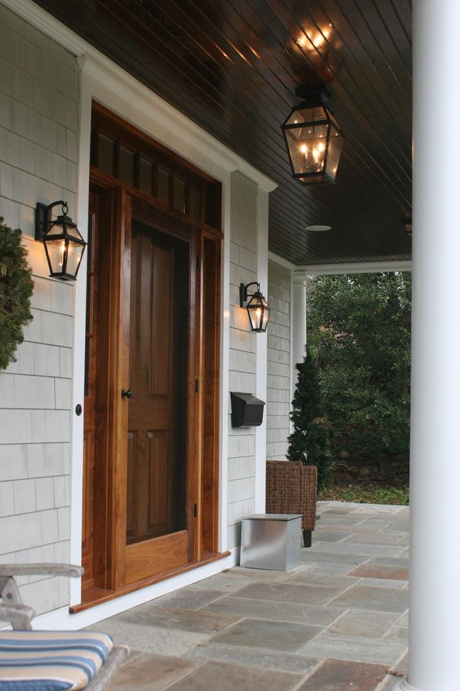 Outdoor Door Knobs with Traditional Entry  and Covered Entry Dark Ceiling Front Door Front Porch Lanterns Mailbox Outdoor Lighting Painted Wood Screen Door Shingle Siding Stone Paving Storm Door White Trim Wood Front Door Wreath