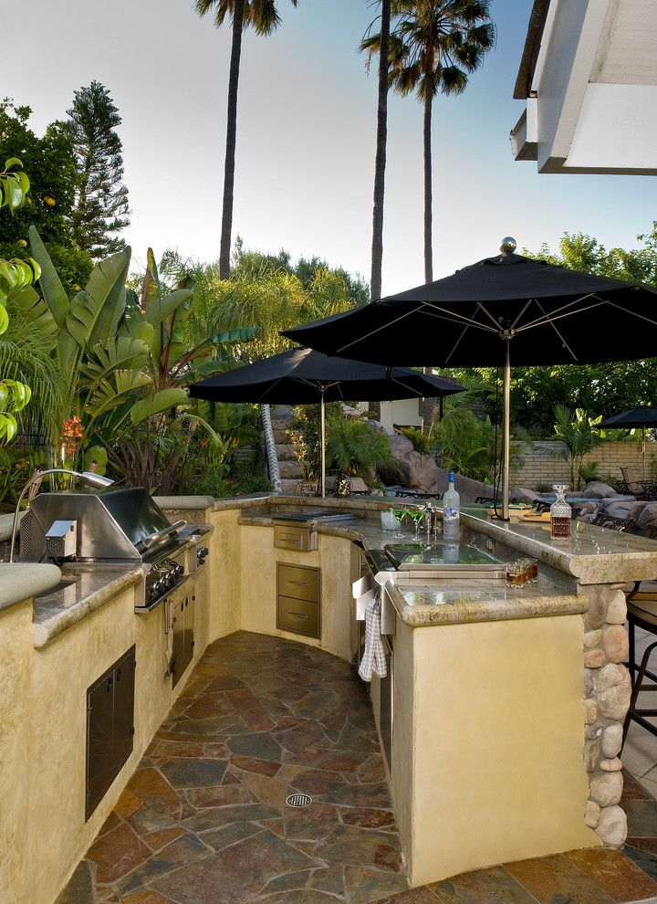Outdoor Griddle Built in with Tropical Patio  and Black Outdoor Umbrella Black Umbrella Grill Integrated Grill Outdoor Bar Outdoor Counter Outdoor Kitchen Palm Tree Rock Counter Stone Patio Tree Tropical Landscape Tropical Plants