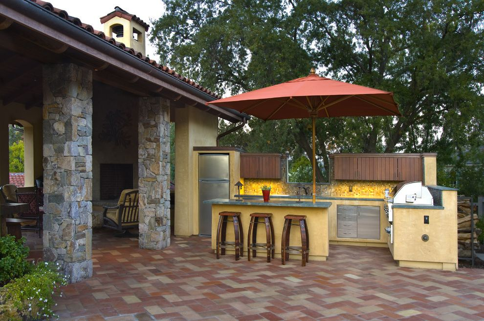 Outside Umbrella Stand   Mediterranean Patio Also Counter Stools Covered Patio Outdoor Kitchen Stainless Steel Stone Posts Stucco Tile Floor Tile Roof Umbrella