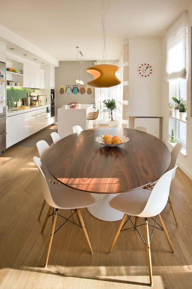Oval Dining Table Pedestal Base   Contemporary Dining Room  and Eames Chair Orange Pendant Light Tulip Table White and Gray Walls White High Gloss Kitchen White Kitchen White Molded Plastic Eames Chair White Roman Shades White Vases Wide Plank Flooring