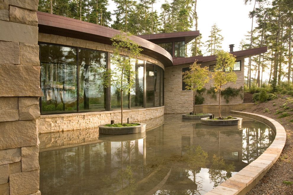 Oversized Hangers with Contemporary Exterior and Butterfly Roof Concrete Planters Curved Room Floor to Ceiling Windows Oversized Windows Picture Windows Pond Slanted Roof Stone Exterior Stone Siding Stone Trim Water Feature Window Wall