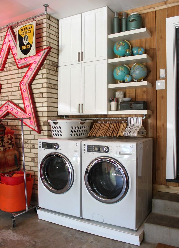 Oversized Hangers with Eclectic Laundry Room and Brick Walls Clothes Rack Concrete Floor Concrete Steps Floating Shelves Pipe Slab Floor Star Sign Thermos Washer Dryer White Appliances White Cabinets White Casing Wood Paneling World Globes