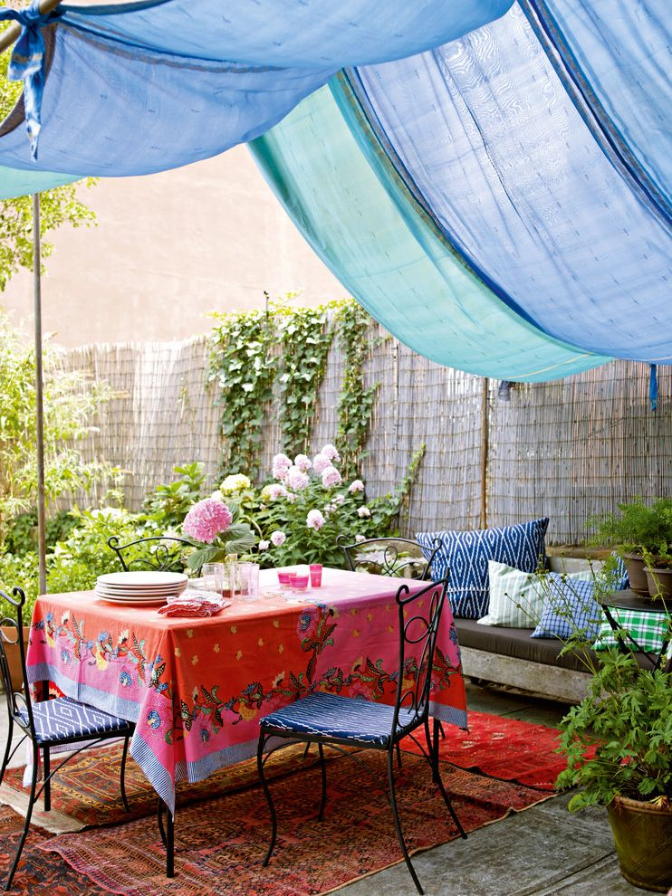 Patio Swing Set with Canopy   Shabby Chic Style Patio  and Bamboo Fence Bench Blue Canopy Blue Chair Cushions Colorful Outdoor Dining Persian Rug Table Linens Urban Wrought Iron Dining Table Set