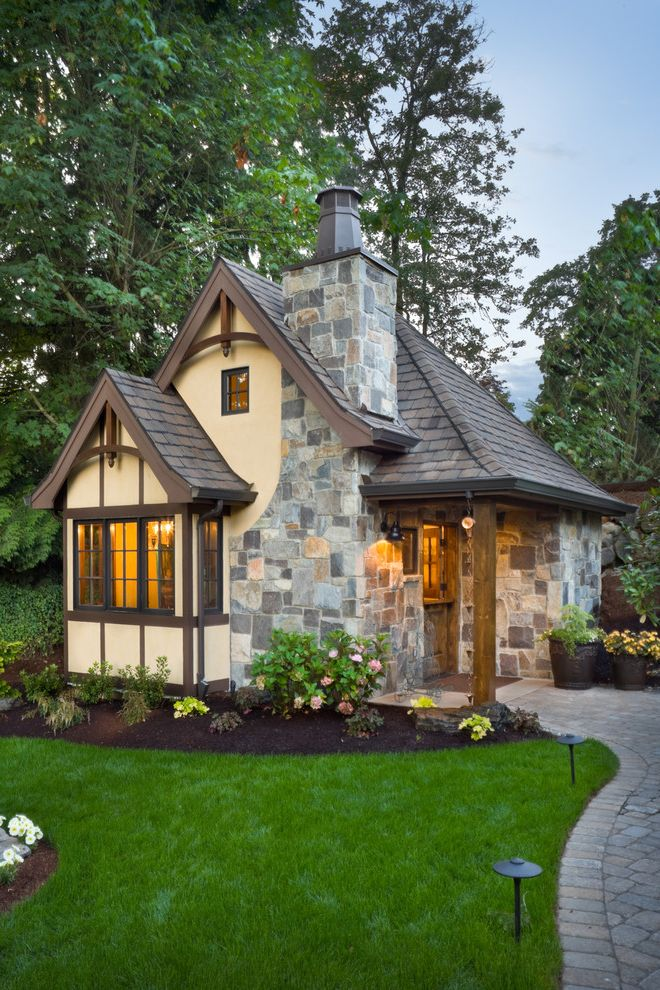 Pats Manor Homes   Traditional Exterior  and Brick Path Brown Trim Charming Cottage Style Cream Walls Cute House Dusk Flower Bed Front Door Garden Lighting Gray Roof Outdoor Lighting Small House Square Window Stone Fireplace Stone Wall Stucco Tudor Style