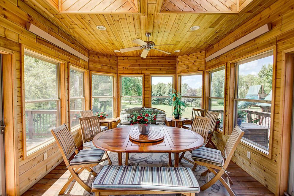 Pavillion Agency Inc with Craftsman Sunroom  and Ceiling Fan Medium Wood Dining Chair Round Medium Wood Dining Table Wood Panel Ceiling Wood Paneled Walls
