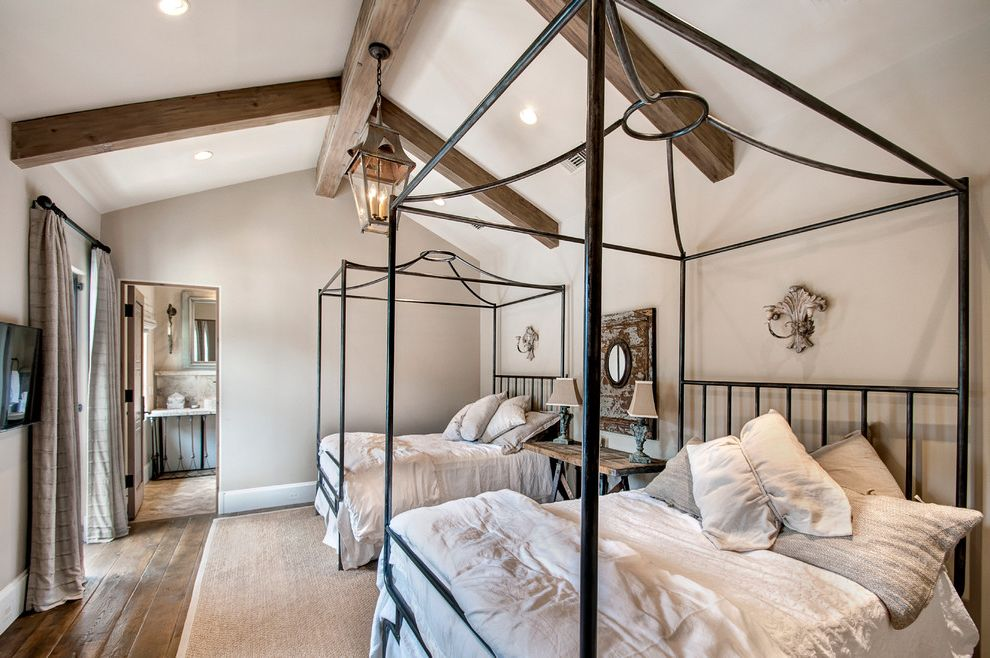Pavillion Agency Inc with Mediterranean Bedroom  and Beige Area Rug Four Poster Canopy Bed Gray Curtains Lantern Pendant Recessed Lighting Vaulted Ceiling Wall Mounted Tv White Bedding Wood Beams