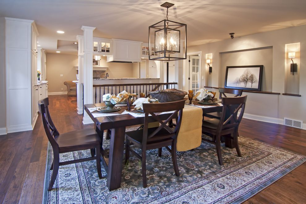 Pewter Light Fixtures with Traditional Dining Room  and Alcove Area Rug Chandelier Dark Stained Wood Dining Table Recessed Panel Staircase Wall Sconces White Painted Cabinets Wood Floor