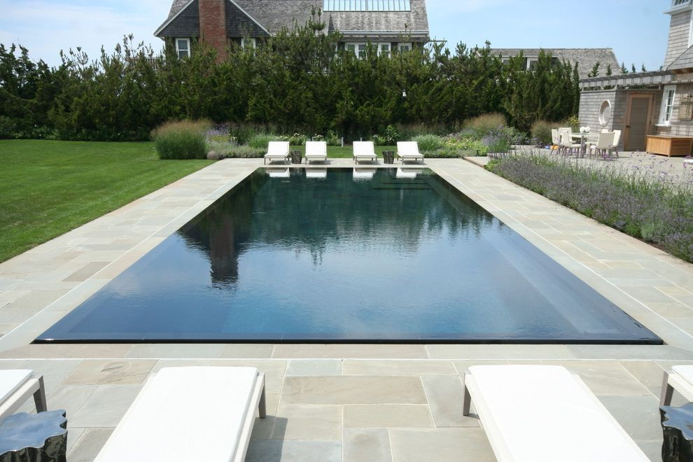 Pinnacle Building Services with Beach Style Pool  and Chaise Lounge Disappearing Edge Pool Flagstone Grass Infinity Pool Lawn Patio Furniture Purple Flowers Screen