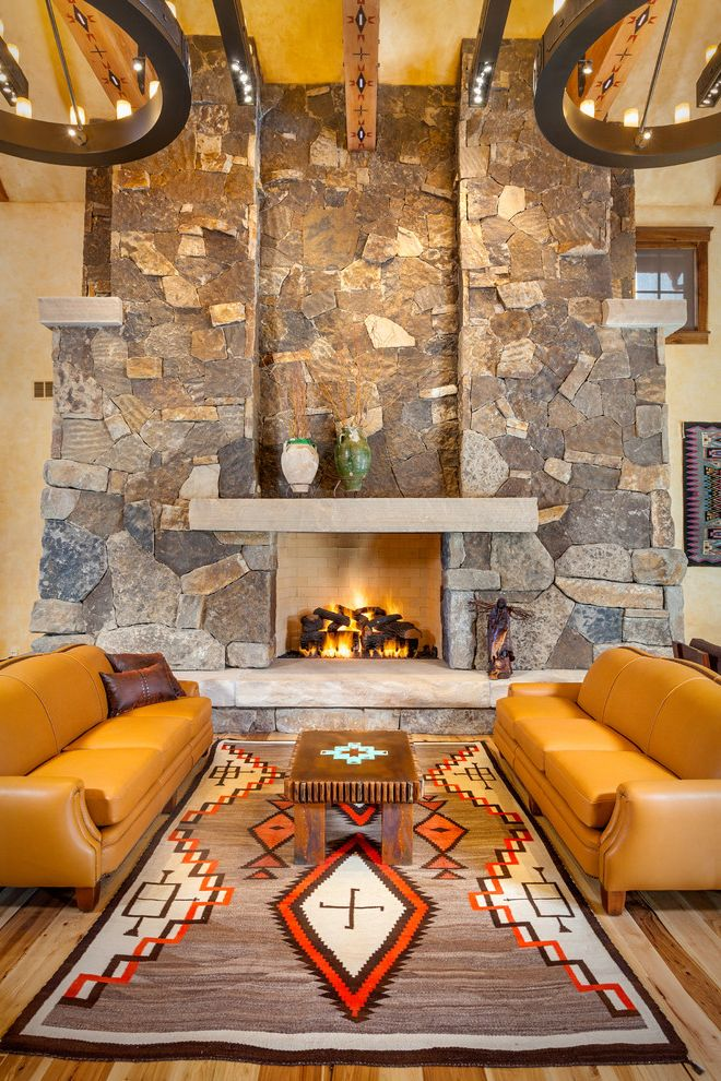 Plae Flooring   Southwestern Living Room  and Brown Leather Pillows Custom Rugs Exposed Beams Fireplace Mantles Iron Light Fixtures Leather Furniture Massive Stone Fireplace Mountain Home Navajo Rug Rustic Great Room Stone Fireplace Yellow Couches