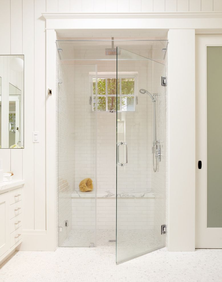 Polished Brass Shower Fixtures with Traditional Bathroom Also Baseboards Curbless Shower Frameless Shower Door Mosaic Tile Rain Showerhead Shower Bench Shower Window Subway Tile Tile Floors White Tile White Trim Wood Paneling Zero Threshold Shower
