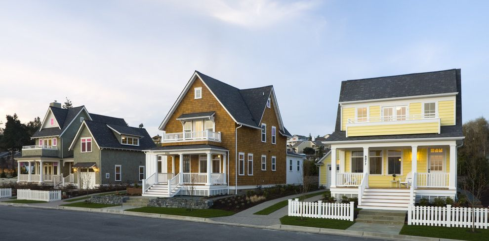 Post Community Credit Union with Traditional Exterior  and Balcony Cape Cods Covered Dormer Gable Roofs Green Lawn Porch Shingle Siding Two Story White Painted Trim Yellow
