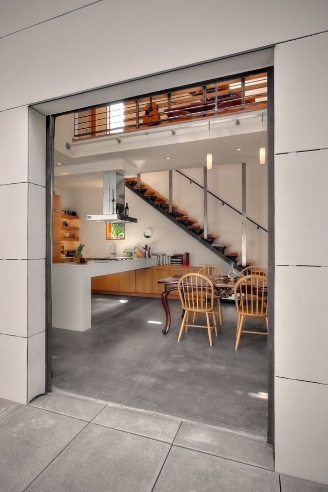 Poured Concrete Floors with Industrial Dining Room Also Ceiling Lighting Concrete Flooring Floating Staircase Industrial Loft Open Floor Plan Open Risers Open Staircase Pendant Lighting Range Hood Recessed Lighting Windsor Chair