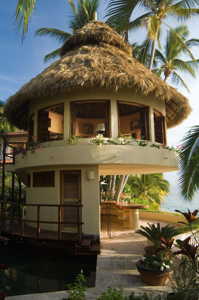 Quonset Hut for Sale   Tropical Exterior Also Architectural Photography Cabana Bar and Office with Ocean View Cone Roof Exterior Grass Roof Lookout Louvered Doors Ocean View Palm Trees Potted Plants Steps Tropical Plants View Wood Railing
