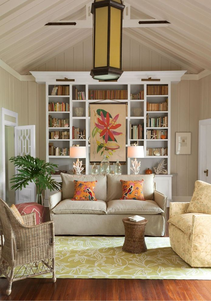 Rattan Bookshelf   Traditional Living Room Also Beach Beach Living Beige Sofa Built in Shelving Crown Molding Large Chandelier Living Room Orange Pillows Panel Walls Pitched Ceiling Seaside Small Palm Tree Tropical White Door White Trim Wood Floor