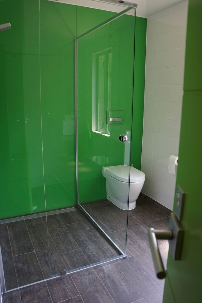 Rear Outlet Toilet with Contemporary Bathroom  and Coloured Glass Contemporary Toilet Frameless Shower Geberit Glass Shower Glass Wall Green Wall Inwall System Small Bathroom Timber Tiles Toilet White Tile Wall Wood Floors