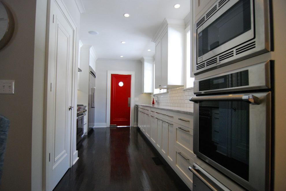 Red Door Consignment with Contemporary Kitchen  and Ceiling Lighting Dark Floor Galley Kitchen Panel Door Pantry Door Recessed Lighten Red Accent Red Door Stainless Steel Appliances White Kitchen