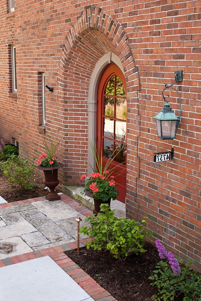 Red Door Consignment with Traditional Entry  and Curb Appeal Garden Ideas Landscape Design Address Number Arched Door Architecture Astilbe Brick Copper Lantern Garden Landscape Limestone Outdoors Plant Pots Planting Bed Red Rusted Steel Urn Wall Sconce