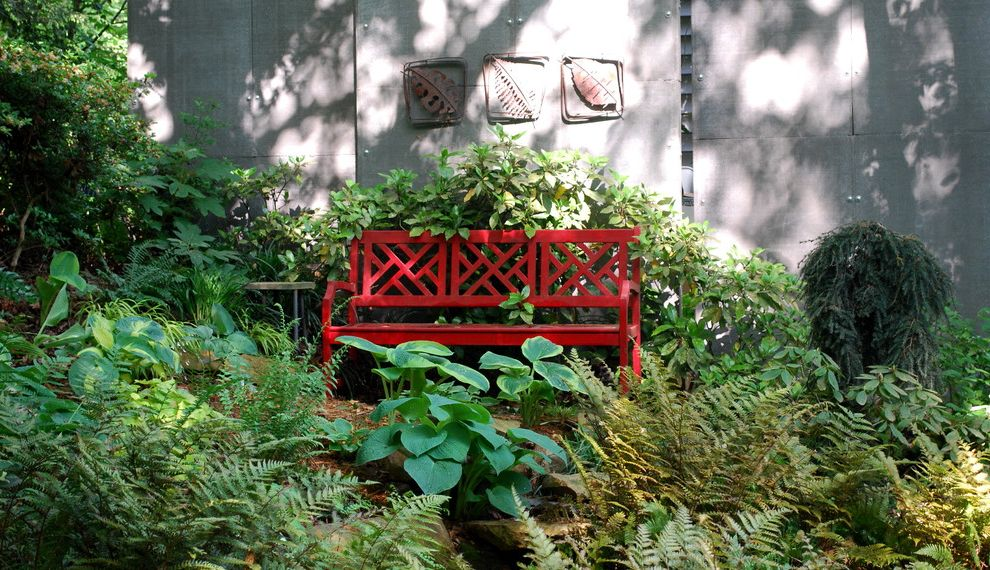 Red Orchid Spa   Eclectic Landscape  and Bench Bushes Concrete Siding Concrete Wall Conifer Ferns Garden Art Garden Bench Hostas Natural Landscape Outdoor Artwork Painted Bench Privacy Screen Red Bench Shade Garden Shrubs Weeping Hemlock Woodland Garden
