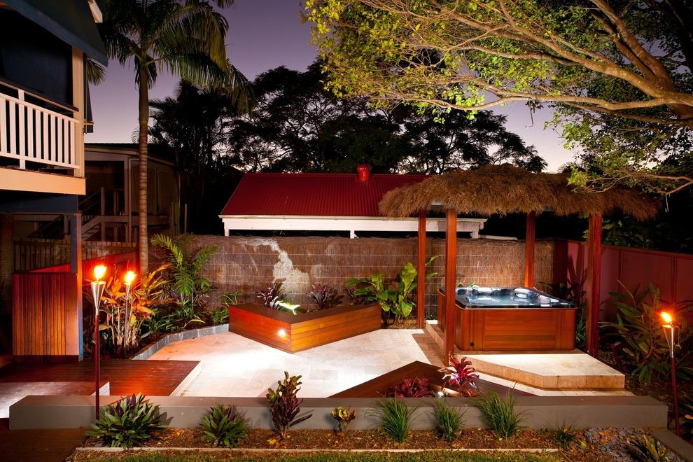 Refined Beauty Day Spa   Tropical Patio  and Bushes Grass Fence Grass Pergola Grass Roof Palm Tree Shrubs Stone Patio Thatch Pergola Thatch Roof Tiki Torch Wood Beam Wood Bench Wood Planters Wood Post