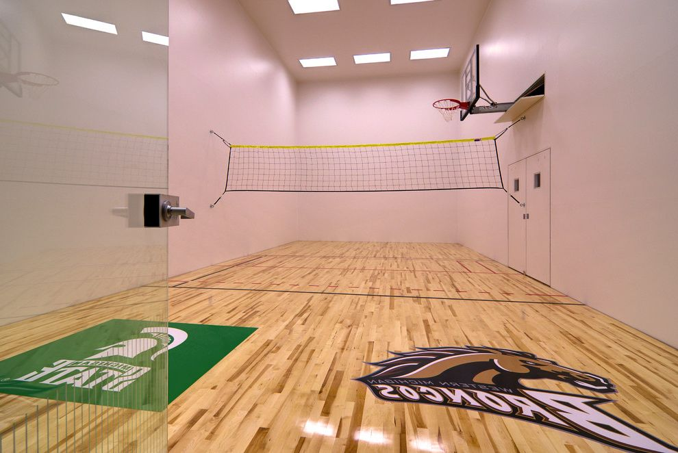 Regulation Volleyball Court   Traditional Home Gym Also Badminton Court Basketball Court Basketball Hoop Basketball Standard Ceiling Lighting Glass Door Hand Ball Court High Ceiling Kids Play Sports Teams Logos Volleyball Net Wood Floor