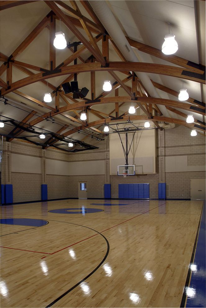 Regulation Volleyball Court with Traditional Home Gym  and Barn Basketball Brick Wall Ceiling Light Curved Beams Exposed Wood Beam Gym Gym Floor Pendant Light Wood Beam Wood Floor