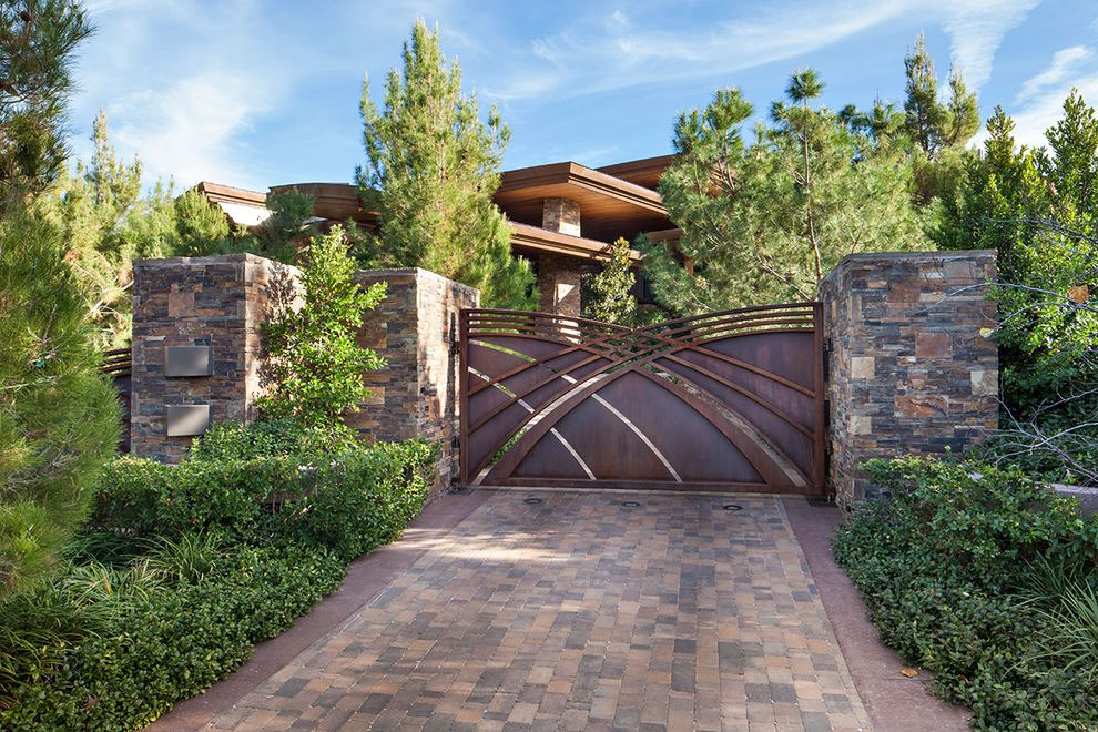 Residential Driveway Gates with Contemporary Landscape Also Artistic Gate Brick Driveway Cantilevered Roof Driveway Gate Eaves Evergreen Trees Pine Trees Shrubs Stone Columns