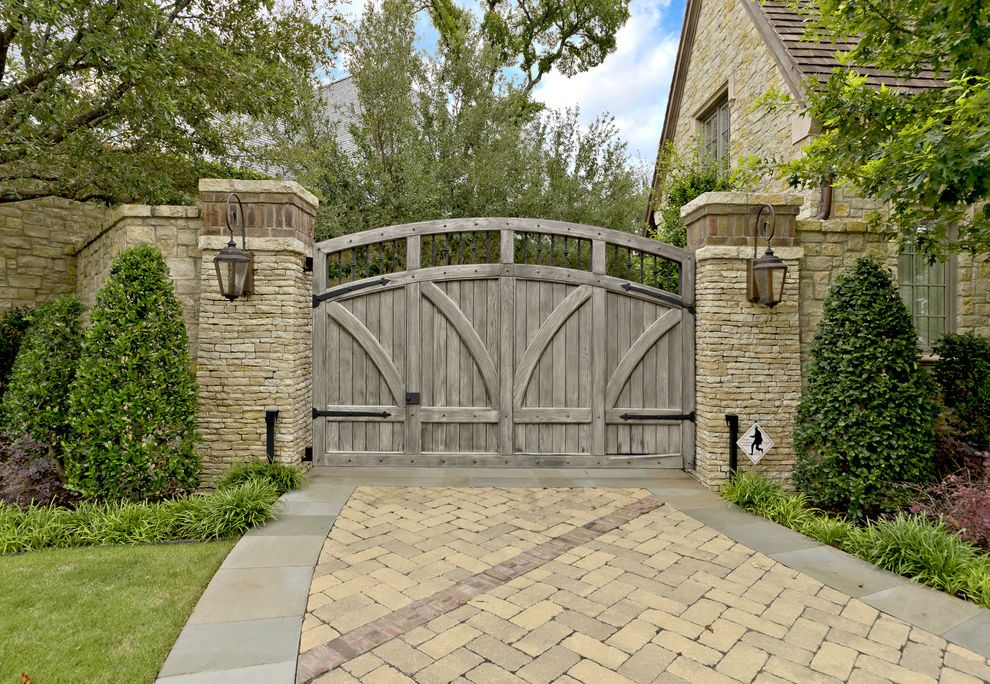 Residential Driveway Gates with Traditional Landscape Also Driveway Entry Grass Hardscape Herringbone Pattern Path Pavers Plants Sconce Shingle Roof Stone Exterior Stone Fence Trees Walkway Wood Gate