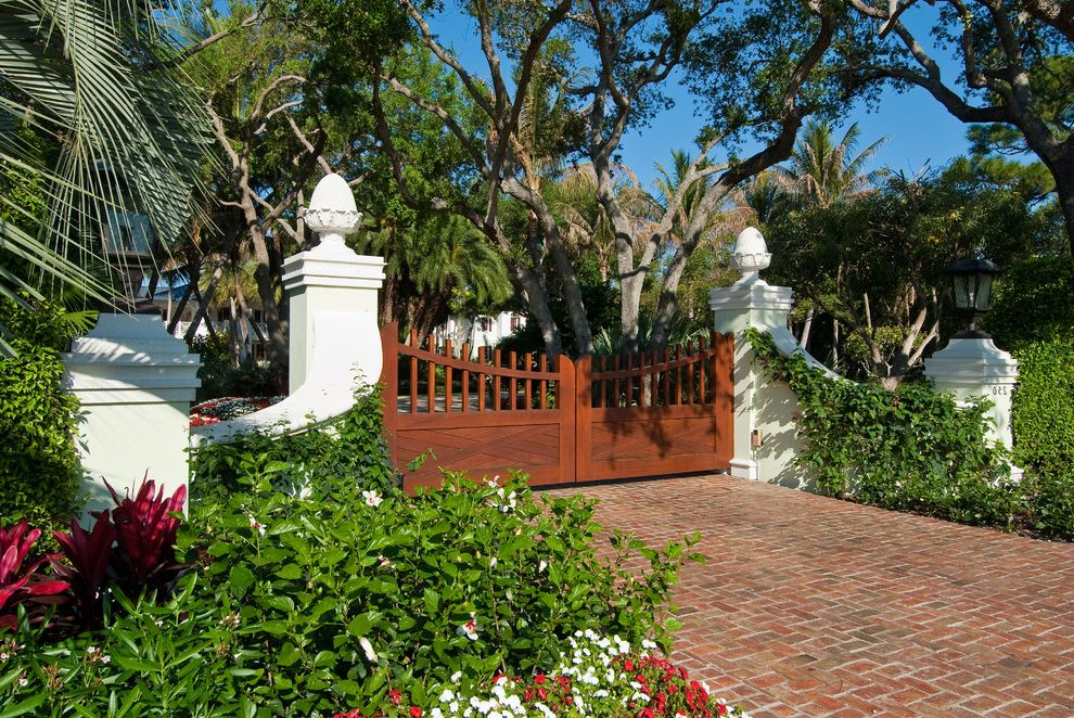 Residential Driveway Gates with Tropical Landscape  and Brick Driveway Gate Outdoor Lantern Palm Tree Red Flowers Trees Vines White Column White Flowers White Wall Wood Gate