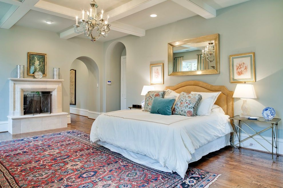 Restoration Hardware Houston with Traditional Bedroom  and Arched Entry Beige Headboard Chandelier Coffered Ceiling Gold Mirror Grey Wall Large Rug Recessed Lighting Small Mantel Small Nightstand Tile Fireplace Wood Floor