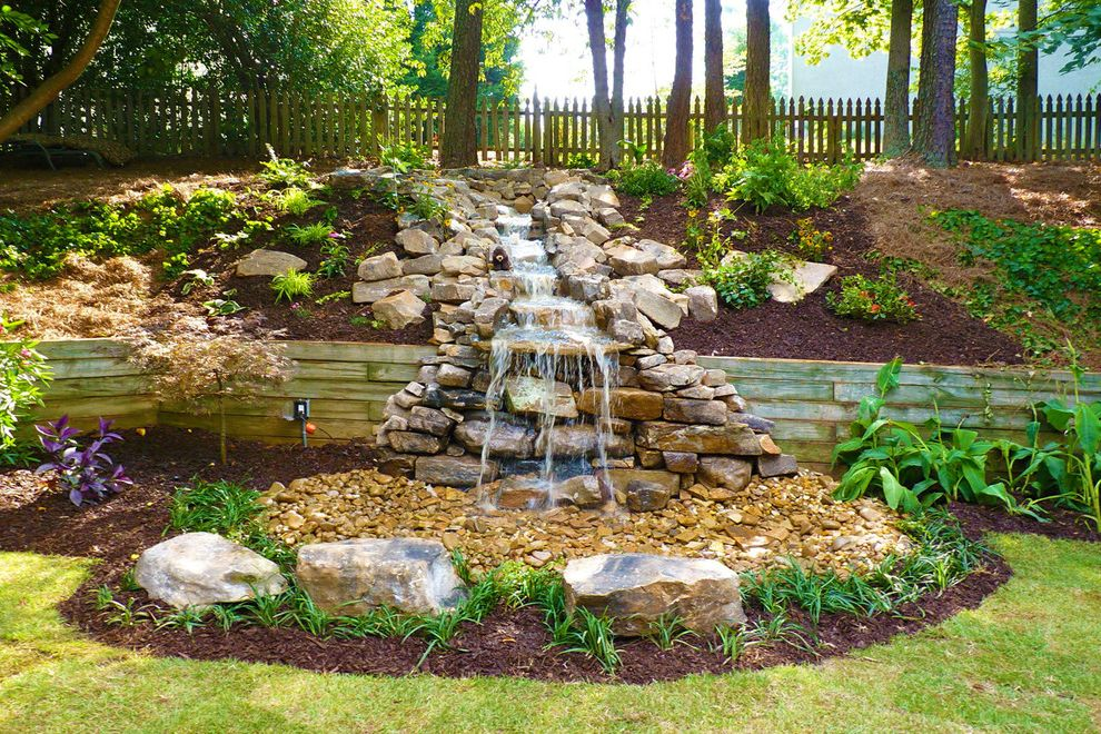 Retaining Walls Omaha Ne   Traditional Landscape  and Backyard Landscaping Boulders Flowers and Plants Grass Hillside Landscaping Mulch Rock Waterfall Sunlight Wood Picket Fence Wood Retaining Wall
