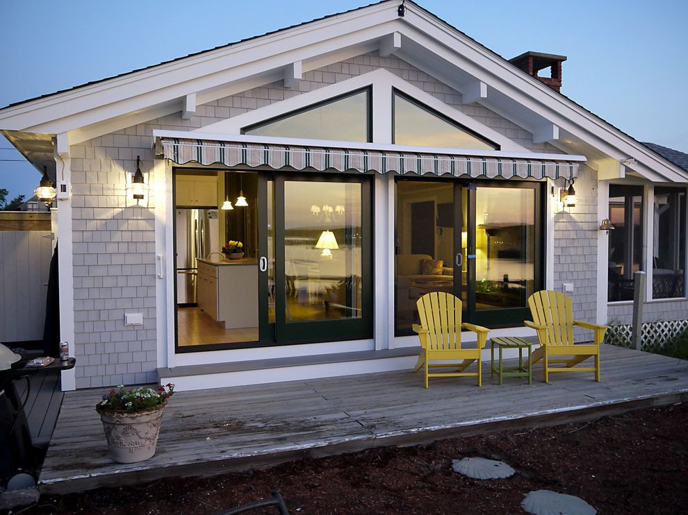 Retractable Glass Doors with Beach Style Exterior Also Adirondack Awning Beachy Deck Eaves Lanterns Outdoor Lighting Overhang Patio Doors Patio Furniture Rustic Shingle Siding Sliding Doors White Wood Wood Molding