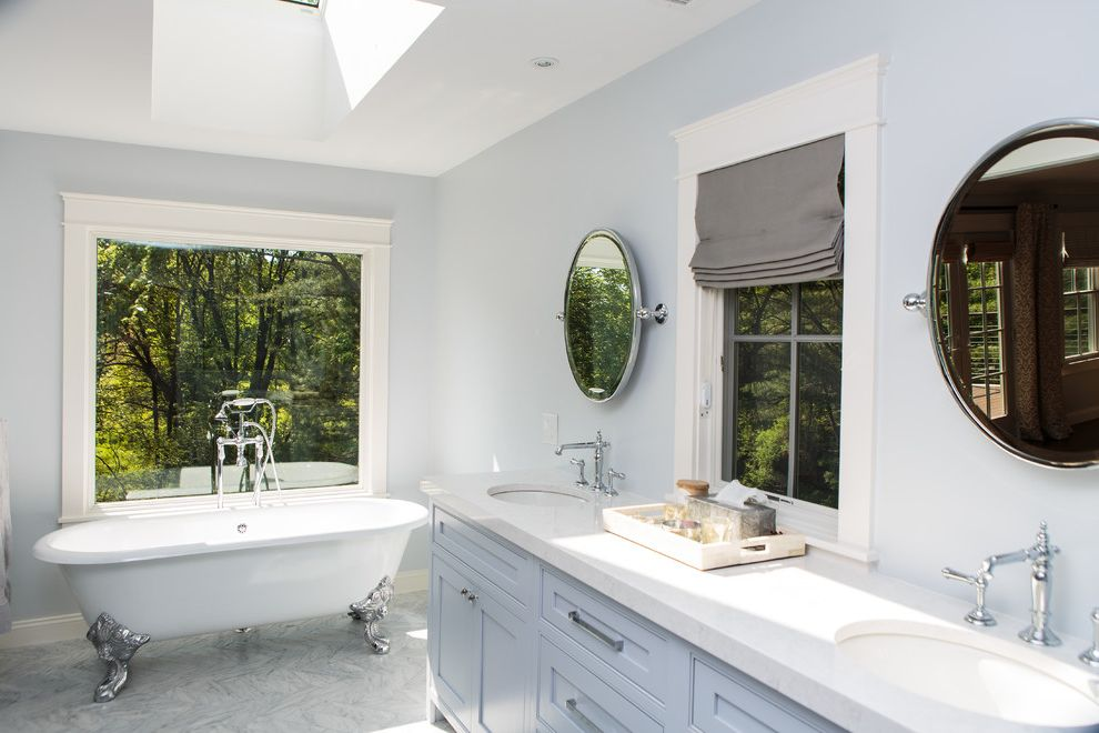 Riverstone Quartz   Transitional Bathroom  and Blue Cabinets Circle Mirror Claw Foot Tub Gray Roman Shades Large Window Above Tub Recessed Lighting Skylight