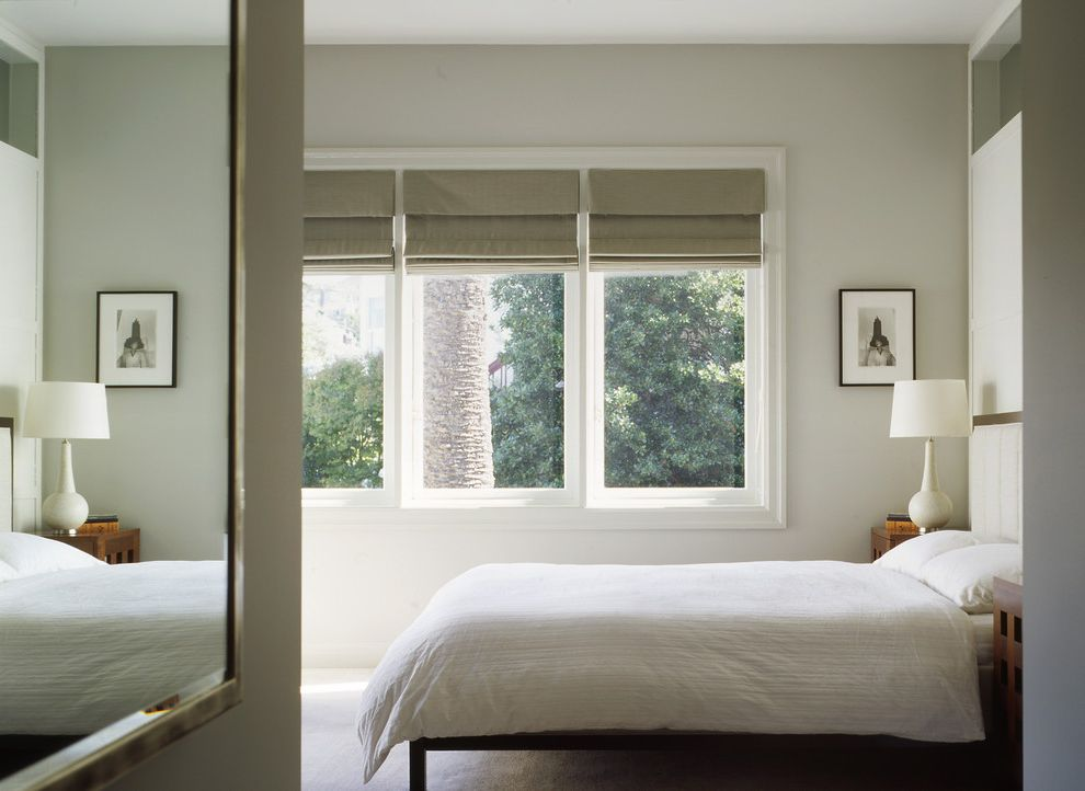 Roll Down Window Shades with Traditional Bedroom  and Drum Lampshade Framed Mirror Grey Wall Minimal Monochromatic Moulding Natural Light Neutral Colors Roman Shades Silver Mirror Table Lamp Wall Art Wall Decor White White Bedding Window Treatments