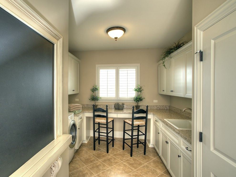Room and Board Outlet with Traditional Laundry Room  and Built in Storage Ceiling Lighting Chalkboard Desk Floor Tile Front Loading Washer and Dryer Rush Seat Chair Sconce Utility Sink White Cabinets