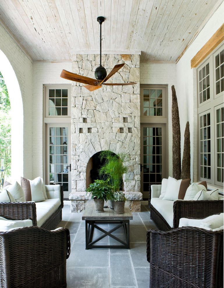 Rustic Outdoor Ceiling Fans   Mediterranean Patio  and Black Straw Seating Outdoor Ceiling Fan Potted Plants Recessed Decoration Transom Windows Wood Ceiling Wood Coffee Table