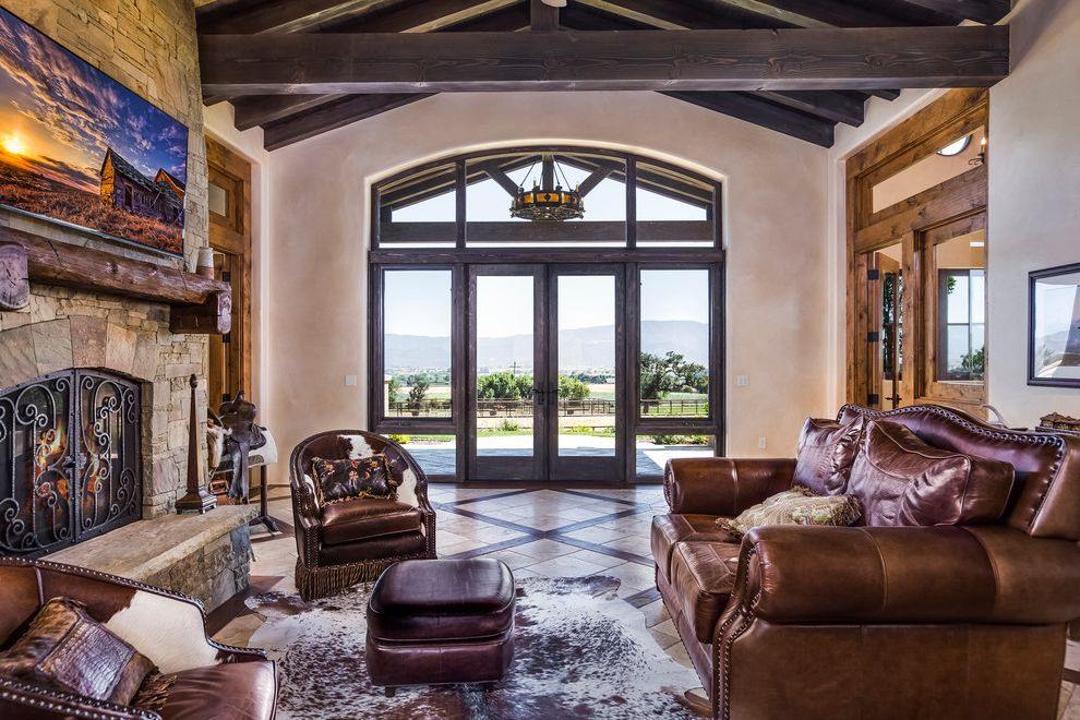 Saddle Leather Couch   Southwestern Living Room  and Animal Sking Rug Exposed Beams French Doors Glass Doors Horse Saddle Leather Couch Nailhead Trim Painting Transom Window Vaulted Ceiling