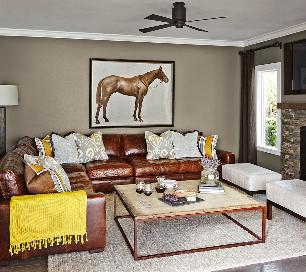 Saddle Leather Couch with Transitional Living Room  and Braided Rug Ceiling Fan Decorative Pillows Horse Art Leather Sectional Ottomans Reclaimed Wood Table Wood Yellow Accents Yellow Throw