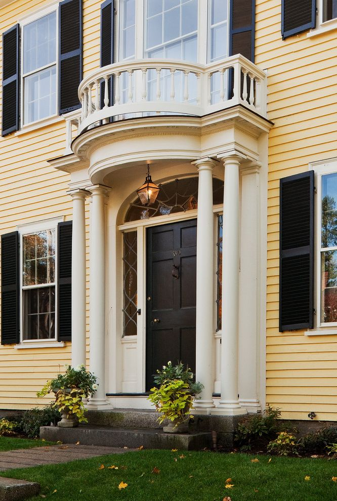 Sea Captains House   Traditional Entry Also Arched Window Beige Molding Beige Trim Black Front Door Black Window Shutter Column Grass Hanging Lantern Lawn Pillar Railing Yellow Exterior Yellow Siding