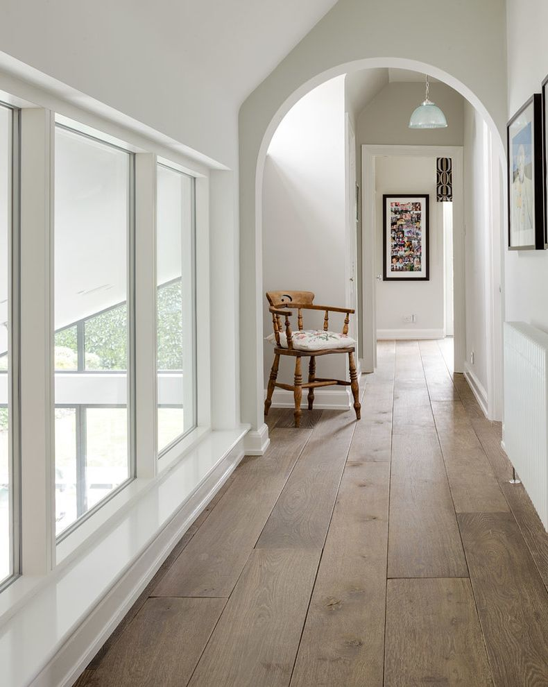 Shamrock Plank Flooring with Transitional Hall  and Archway Coastal Driftwood Oak Floors English Country Grey Grey Wood Floors Hallway Industrial Landing Natural Real Wood Reclaimed Wood Floors Slanted Ceiling White Walls Wood Floor Wooden Planks
